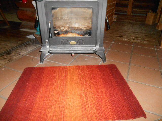 薪ストーブ前に赤いウールラグ